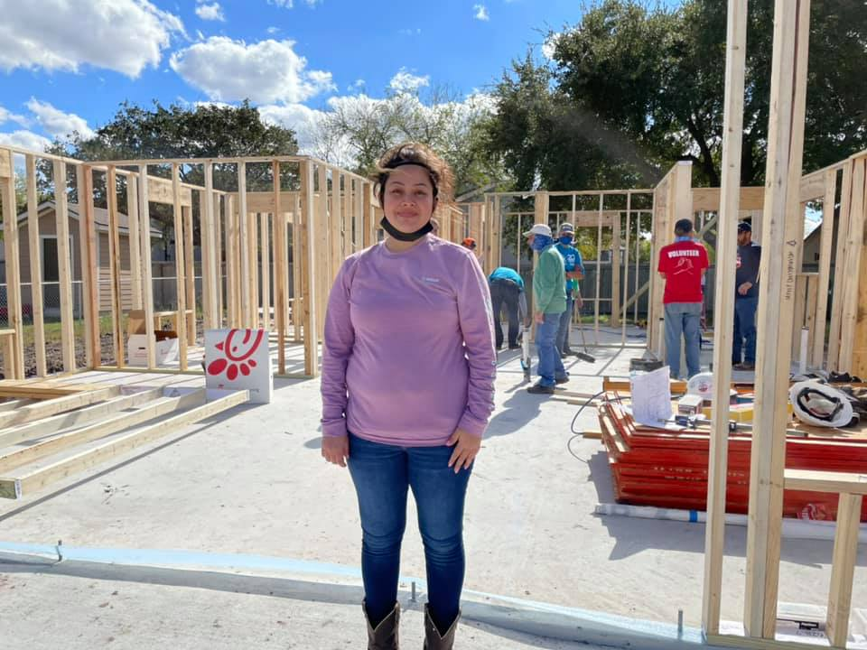 Maressa standing in front of the walls of her home after they were built at a Help Build Hope event in Texas